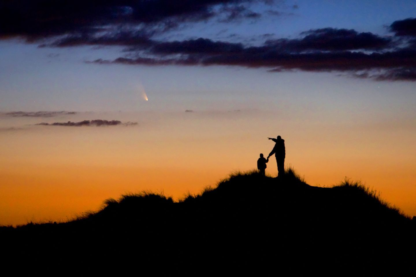 Father and son observe comet PanSTARRS. A father and his young son watch the evening display of comet PanSTARRS on First Encounter beach, Eastham, Massachusetts, USA. The photographer had spent weeks preparing