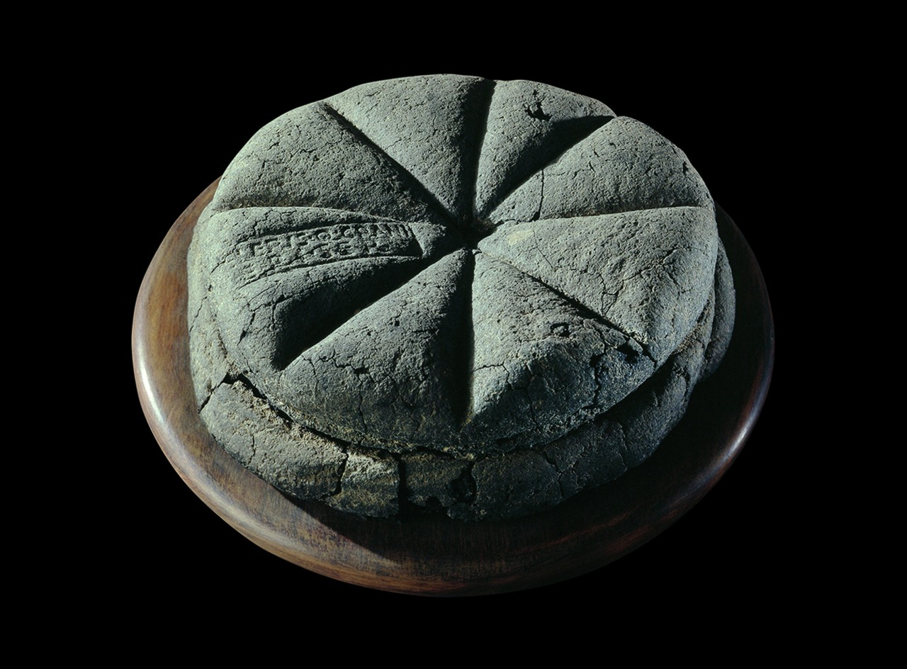 A carbonised by volcanic ash loaf of bread with the stamp 'Property of Celer, Slave of Q. Granius Verus', Herculaneum (near Pompeii), 79 AD